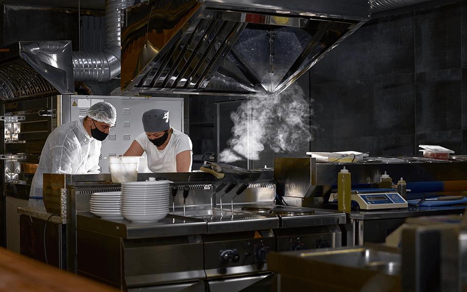 Chefs preparando ficha técnica em uma cozinha de restaurante corporativo