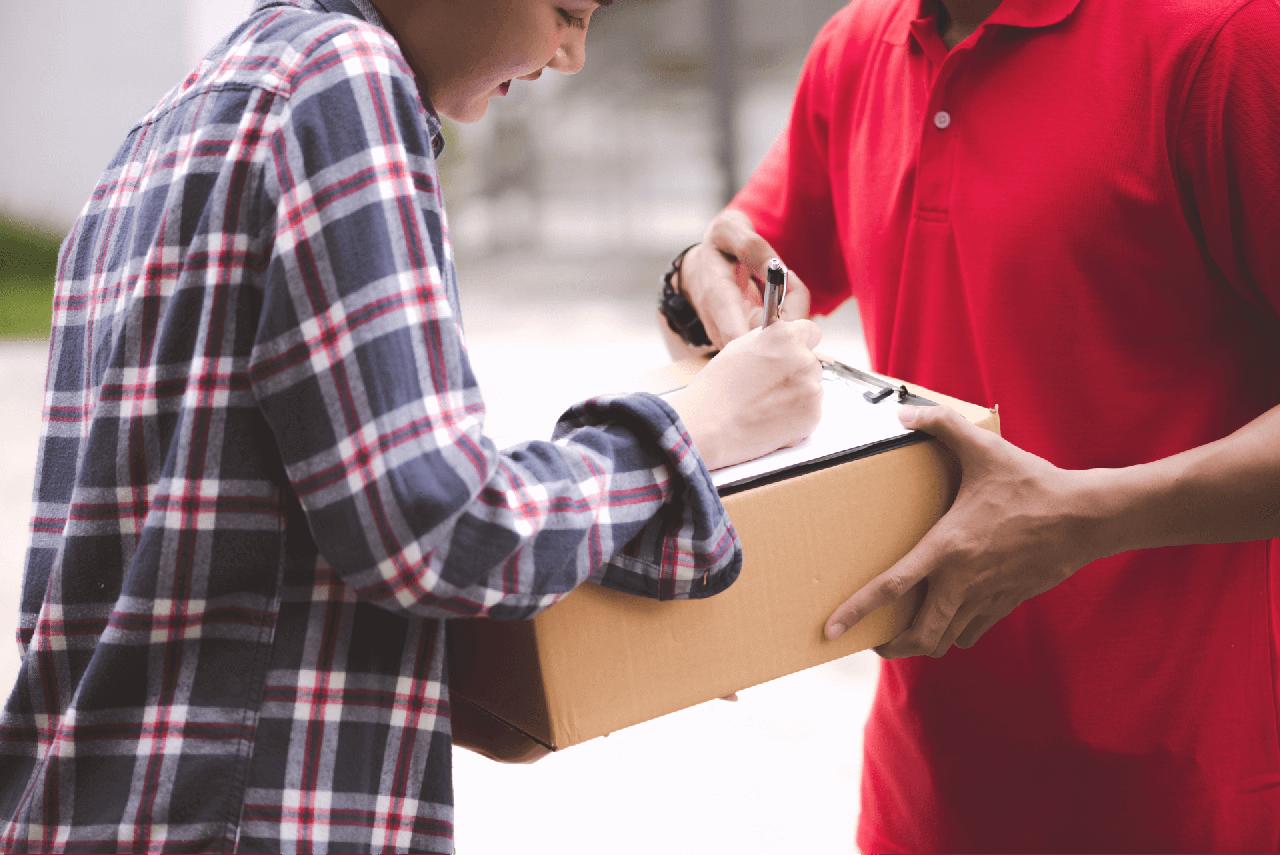 Pessoa assinando o termo de entrega para receber um pedido