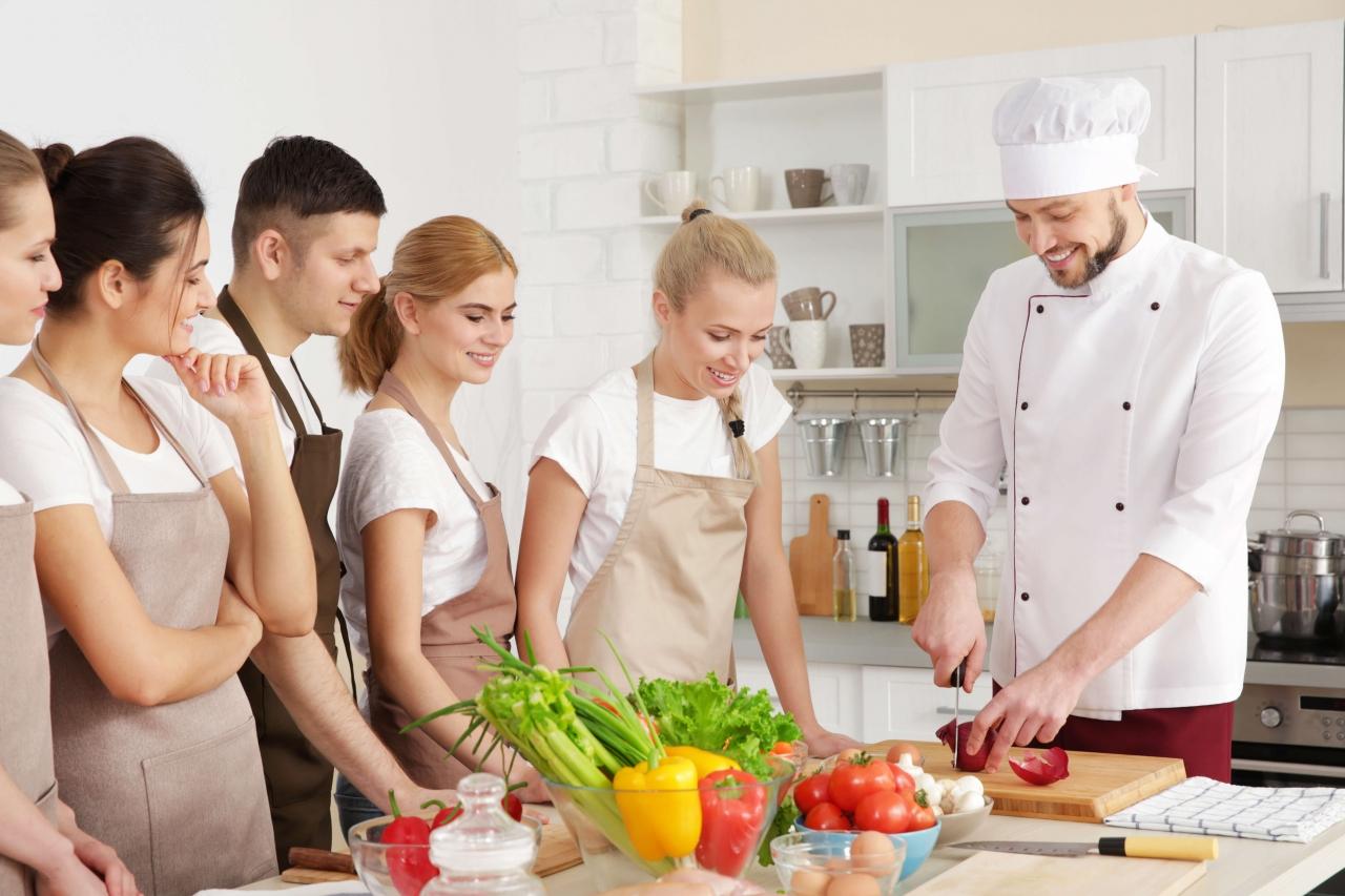 Chef demonstrando como preparar um prato para alunos em uma cozinha